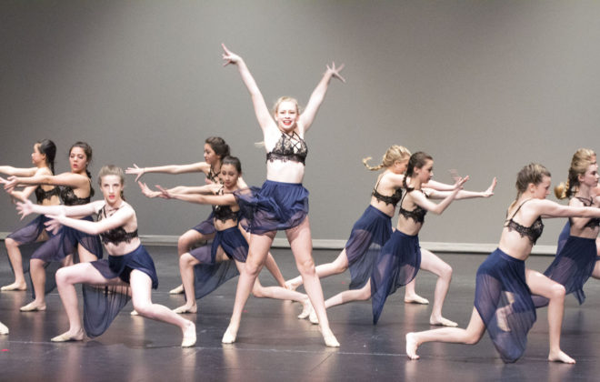 Teenage dancers perform a contemporary routine on stage.