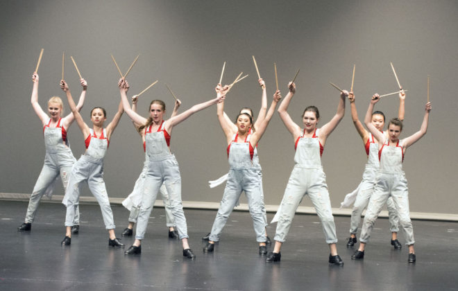 Teen dancers perform a tap routine with drumsticks.