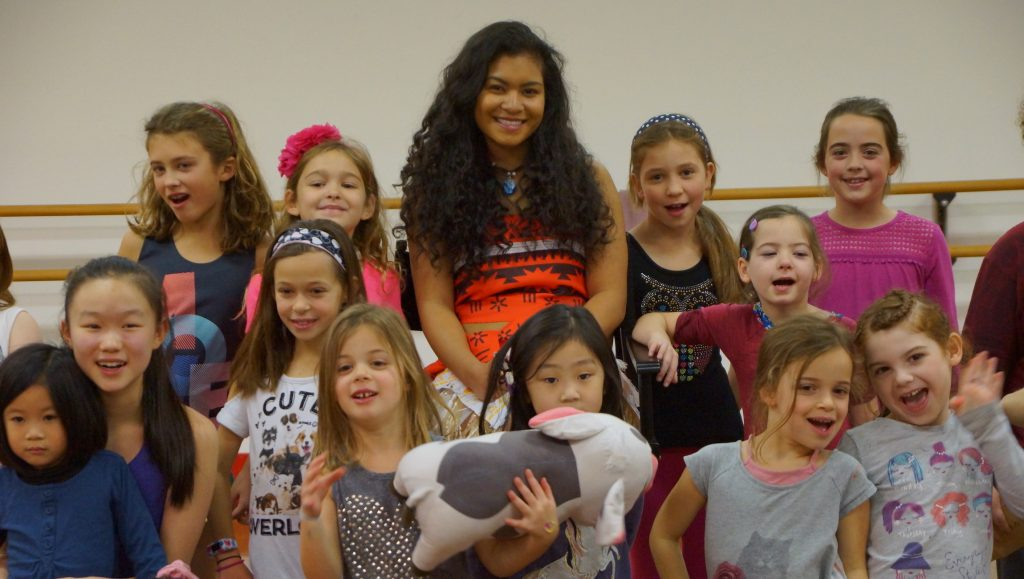 A young woman dresses as Moana and greets students and summer dance camp.