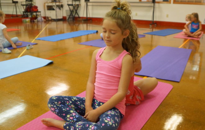 Young students participate in a yoga class.