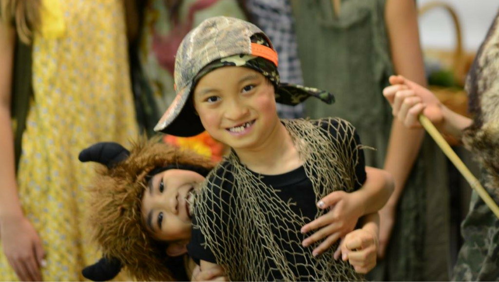 A boy wearing a baseball cap and netting and a girl wearing a furry hat act out the lost boys scene from Peter Pan.